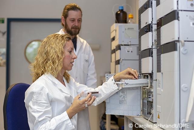 Dr. Weber stellt ein sitzt im Kittel vor einer HPLC-Anlage und hält mehrere Proben in der rechten Hand. Mit der Lin-ken setzt sie ein Röhrchen in das Gerät ein. Im Hintergrund steht ein Kollege, ebenfalls im Kittel.